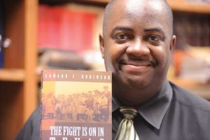 Smiling African American Man holding a book