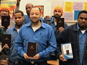 a group of men in prison clothes holding Bibles