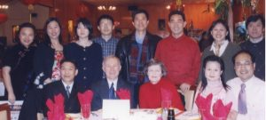 A group of Chinese people gathered around a table with an older white couple
