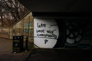 "wall with graffiti text ""Let's Love Our Community"""